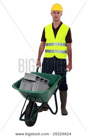 Man pushing waste material in wheelbarrow