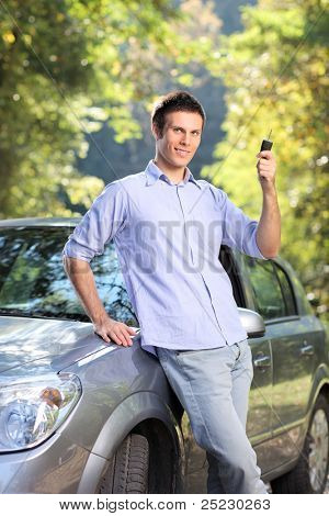 A smiling male holding a car key posing next to his automobile