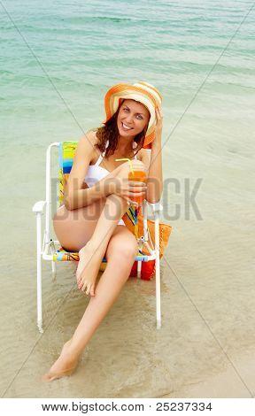 Retrato de niña feliz en bikini con vidrio con jugo fresco mientras se relaja por agua