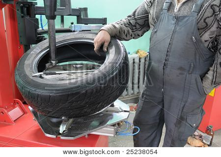 The Car Mechanician Changes A Tyre Cover On An Automobile Wheel