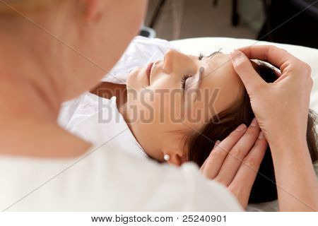 Over the shoulder shot of professional acupuncturist placing needle in face of patient