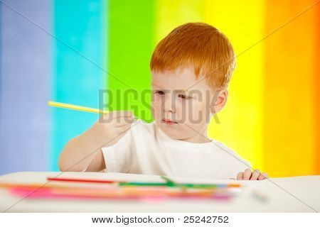 Redheaded adorable boy drawing with yellow pencil on rainbow background