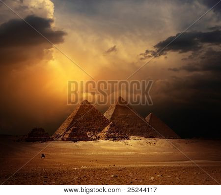 Great pyramids in Giza valley with yellow dark clouds on the background