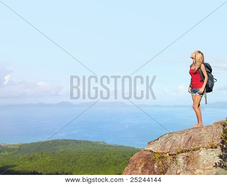 Woman with backpack standing on a top of a mountain and looking to somewhere