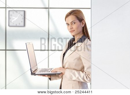 Attractive young businesswoman using laptop, smiling in office.?