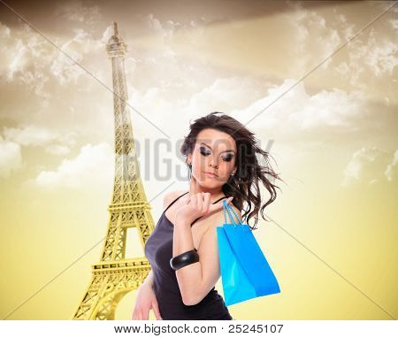 Beautiful woman holding many shopping bags with the Eiffel Tower on background