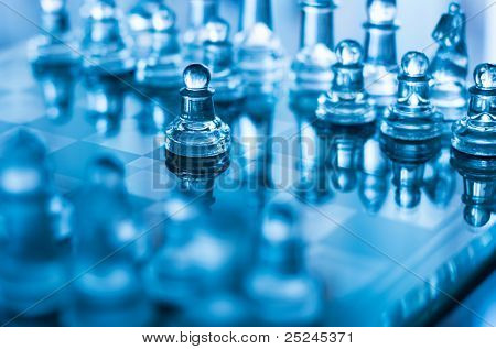glass chess pawn in front with shallow depth of field in blue light