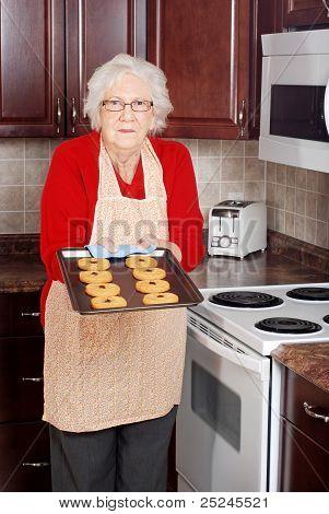 mujer Senior con galletas horneadas frescas