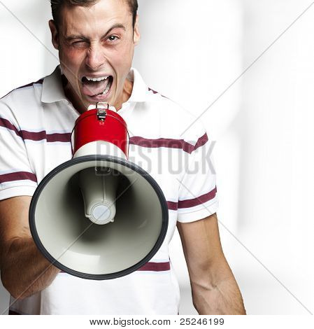 portrait of young man shouting with megaphone indoor