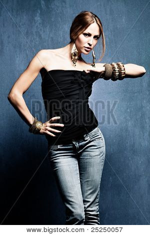 young woman in blue jeans and oriental jewelry studio shot