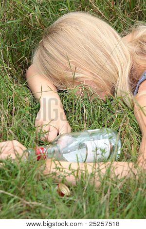 Teen alcohol addiction (drunk teen with vodka bottle)