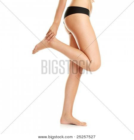 Woman holding sore ankle, on white background.