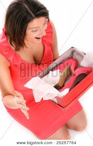 A picture of a happy surprised woman holding her shoes over white background