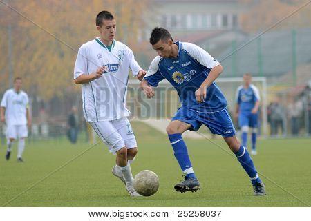 KAPOSVAR, HUNGARY - NOVEMBER 6: Krisztian Keresztes (in white) in action at the Hungarian National Championship under 19 game Kaposvar vs. Nagybajom November 6, 2011 in Kaposvar, Hungary.