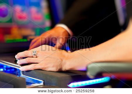 Couple in Casino on a slot machine winning and having fun - only hands to be seen