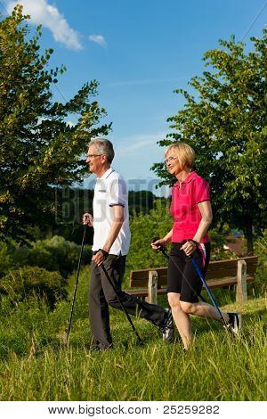Nordic Walking - Happy mature or senior couple doing sports in summer outdoors