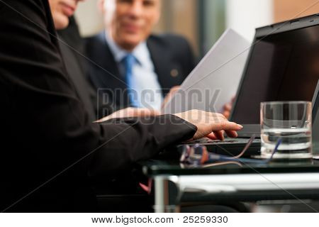 Business - team meeting in an office with laptop, the woman in front is typing