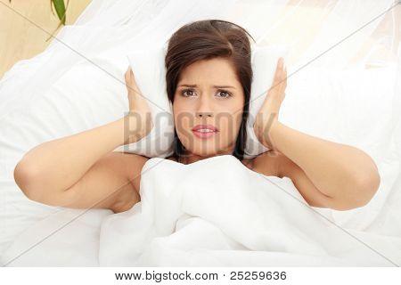 Feminino deitado na cama e fechar seus ouvidos com travesseiro