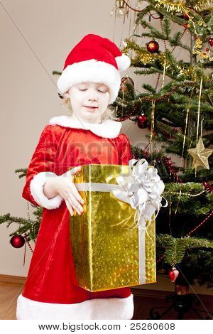 little girl as Santa Claus with Christmas present