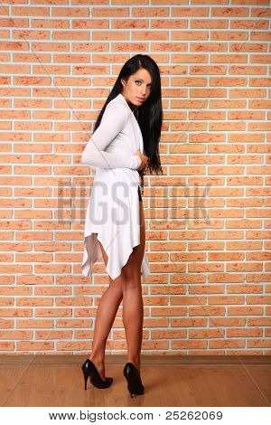 beautiful elegant woman with black hair stands back to camera near brick wall; full body