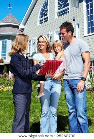 Família feliz com corretor de imóveis agente perto de casa nova.