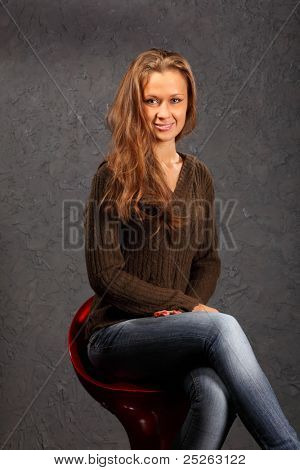 beautiful smiling girl wearing blouse and jeans sits on red chair in studio