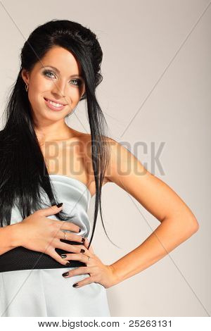 brunette smart woman with black manicure looks inscrutable and smiling