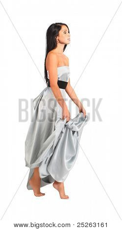beautiful woman wearing long silver dress goes on tiptoe and holds hem isolated on white; full body