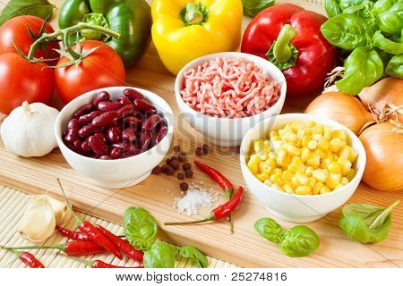 Raw ingredients for a chili con carne, including kindey beans, bell peppers, chili peppers, mincemeat, corn, tomatoes, onions and spices