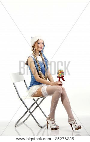 Pretty snow maiden sitting on a white chair holding a lollipop