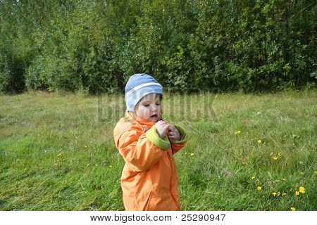 Happy Little Beautiful Girl Wearing Orange Jacket Looks At Piece Of Grass And Wonderson