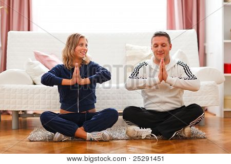 Young Pregnant Woman With Husband Doing Yoga At Home