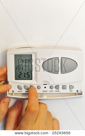 hand pressing button on digital thermostat
