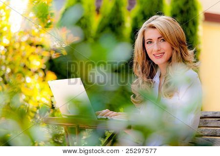 woman with laptop in the garden