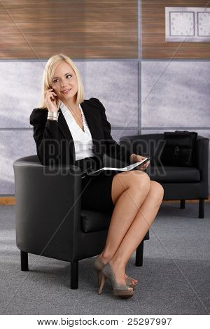 Smiling businesswoman sitting in armchair, talking on mobile phone, smiling, using personal organizer.?