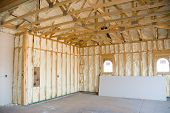 stock photo of rafters  - A room at a newly constructed home is sprayed with liquid insulating foam before the drywall is added - JPG