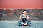 Young attractive woman sitting in yoga pose and smiling outdoor over red wall, image toned. Chinese  poster