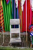 A Weathered Grey Chair In Front Of Multicoloured Cloth Hammocks poster
