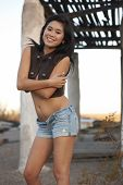 image of breast exposed  - Cute young Asian woman in front of rustic desert building wearing unbuttoned vest exposing cleavage in afternoon light - JPG