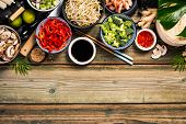 Asian Cuisine Ingredients On Wooden Background, Top View. Vegetables, Spices, Shrimp, Noodles, Sauce poster