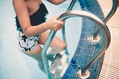 Portrait Of Sexy Woman Is Step On A Pool Ladder., Holiday And Leisure Activities Concept. poster