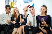 Glamorous girls and guys in smart attire toasting with champagne at birthday party at home poster