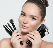 Beauty model girl, makeup artist holding set of make up brushes and smiling. Beautiful brunette youn poster