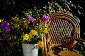 Wicker Chair And A Floor Vase With Flowers In An Autumn Garden, Outdoor Contrast Shot poster