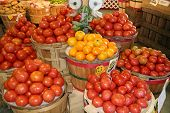 stock photo of farmers market vegetables  - bight red and yellow tomatoes in wooden barrels - JPG