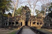 Ancient Ruins Of Ta Prohm Temple In Angkor Wat Complex, Cambodia. Decorated Entrance With Stone Bas- poster