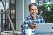 Smiling Happy Mature Asian Man With White Stylish Short Beard Using Smartphone Gadget Serving Intern poster