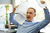 Overworked Angry Businessman Throwing Paper All Over The Office. Stressed Businessman Throwing Chart poster