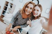 Smiling Mother And Daughter Taking Selfie In Kitchen. Relationship In Family. Holiday At Home. Healt poster