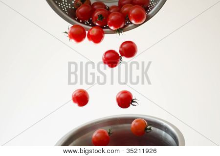 Cherry Tomatoes Tumbling Into Metal Colander